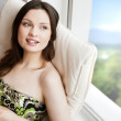 Portrait of smiling beautiful young brunette woman at home — Stock Photo