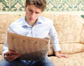 Closeup portrait of young man with newspaper — Stock Photo
