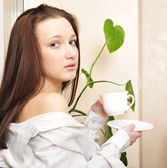 Young woman at home sipping tea from a cup — Stock Photo
