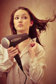 Beautiful woman drying her hair with hairdryer — Stock Photo