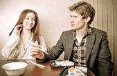 Attractive young couple eating sushi at their home. Retro style photo — Stock Photo
