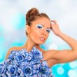 图库照片: Gorgeous woman with blue flower dress over blurred shiny backgro