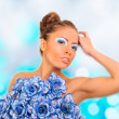 Gorgeous woman with blue flower dress over blurred shiny backgro — Stock Photo