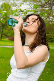 Young woman drinking water at outdoors — Stock Photo