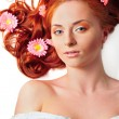 Beautiful woman with flowers in her red hair she is lying relaxe — Stock Photo #6004649