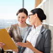 Two business women reading documents — Stock Photo #6004688