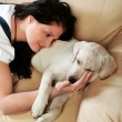 Young woman with dog sitting on sofa — Stock Photo