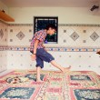 Artistic lifestyle photo of young boy kicking pillow standing on - Stock Photo