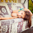 Artistic lifestyle photo of little girl leaning on swing sofa ou - Stock Photo