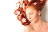 Beautiful woman with flowers in her red hair she is lying relaxe — Stock fotografie