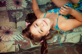 Artistic lifestyle shot of young little girl laying on sofa. Nat — Stock Photo