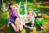 Artistic lifestyle photo of full happy family laying relaxed on — Stock Photo
