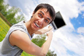 Casual young man pointing at laptop screen — Stock Photo