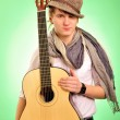 Closeup portrait of cute caucasian man playing the guitar over g — Stock Photo #6026716