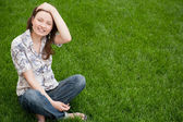 Full length of pretty young woman resting on grass and smiling — Stock Photo
