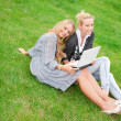 Portrait of two smiling women using laptop on a green meadow at — Stock Photo #6072365