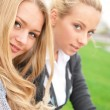 Two women hugging and smiling sitting on the grass at city park — Stock Photo
