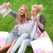 Portrait of two women relaxing on green grass after shopping. Ho — Lizenzfreies Foto