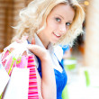 Photo of young joyful woman with shopping bags on the background — Stock Photo #6072395