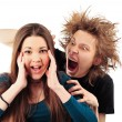 Mad man with funny hairdo tempting young girl for something - Stock Photo