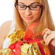 Stock Photo: Beautiful student woman holding a gift isolated on white