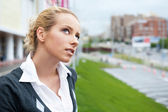 Closeup portrait of a beautiful woman in the city at summer time — Stock Photo