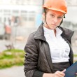 Young architect-woman wearing a protective helmet standing on th — Stock Photo #6128080