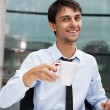 Young businessman having a morning coffee break, sitting at desk — Stock Photo