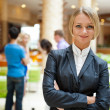 Portrait of a cute business woman with colleagues at the backgro — Stock Photo