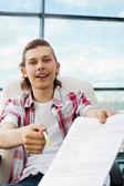 Retrato de um freelancer jovem feliz dando 7rú em branco e caneta — Foto Stock