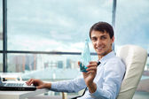 Young business man drinking water sitting relaxed on armchair at — Stock Photo