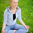 Portrait of young woman meditating in pose of lotus on green gra - Stock Photo