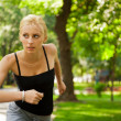 Portrait of young beautiful woman in sportswear running in park. — Stock Photo