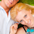 A happy young couple lying on grass — Stock Photo
