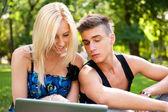 Unga glada leende par med laptop på picknick — Stockfoto