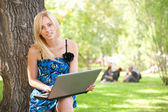 Portrait of a pretty student woman leaning on the tree trunk on — Stock Photo