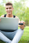 Closeup portrait of young student man using laptop and 3g usb mo — Stock Photo