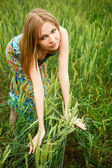 Portrait of young woman stands in a field of wheat with joy — Stock Photo
