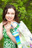 Beautiful woman walking at the summer park holding bags and look — Stock Photo