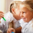 Two little girls gossip in classroom — Stock Photo