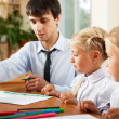Teacher helping students with schoolwork in school classroom. Ho — Stock Photo #6302480