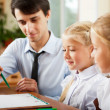 Teacher helping students with schoolwork in school classroom. Ho — Stock Photo