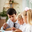 Stock Photo: Teacher helping students with schoolwork in school classroom. Ve