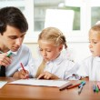 Teacher helping students with schoolwork in school classroom. Ho — Stock Photo #6302491