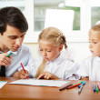 Stock Photo: Teacher helping students with schoolwork in school classroom. Ho