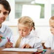 Teacher helping elementary school pupils with their tasks — Stock Photo #6302493