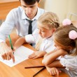 Teacher helping elementary school pupils with their tasks — Stockfoto