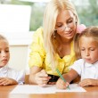 Teacher helps to little girls to make an exercises in classroom — Stock Photo #6302504