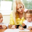 Stock Photo: Teacher helps to little girls to make exercises in classroom