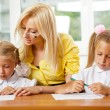 Teacher helps to little girls to make an exercises in classroom — Stock Photo #6302509